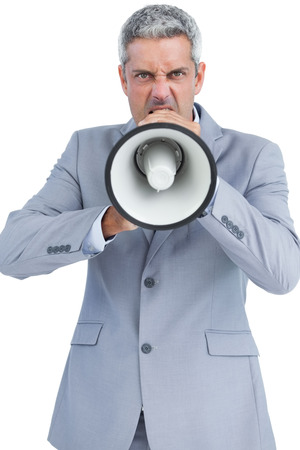 Furious businessman posing with loudspeaker on white background and looking at camera photo