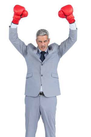 Furious businessman posing with red boxing gloves on white background photo