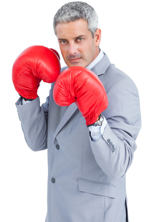 Tough businessman with boxing gloves on white background photo