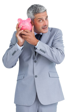 Curious businessman on white background holding piggy bank  photo