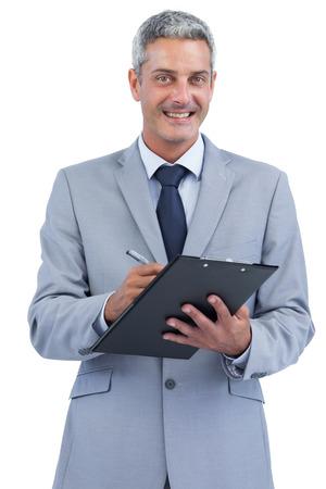 Joyful businessman on white background holding clipboard and taking notes photo