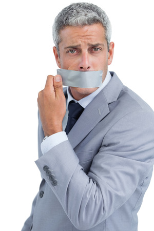 Businessman taking off duct tape on mouth on white background photo