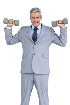 Strong businessman lifting dumbbells on white background photo