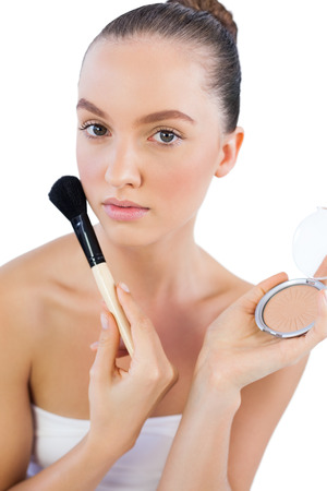 Sensual model with powder compact and powder brush looking at camera photo