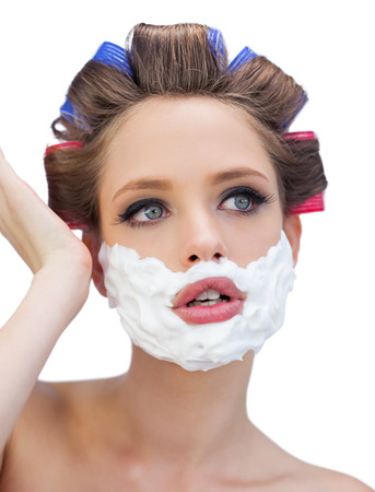 role reversal: Thoughtful model in hair curlers with shaving foam posing on white background