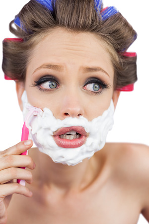 Shocked young model in hair curlers posing with razor on white background photo