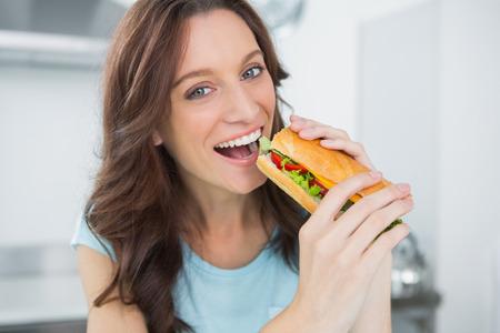adult sandwich: Cheerful brunette in her kitchen eating sandwich Stock Photo
