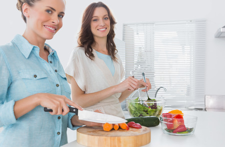 Woman cutting carrots with her friend mixing salad in the kitchen  photo