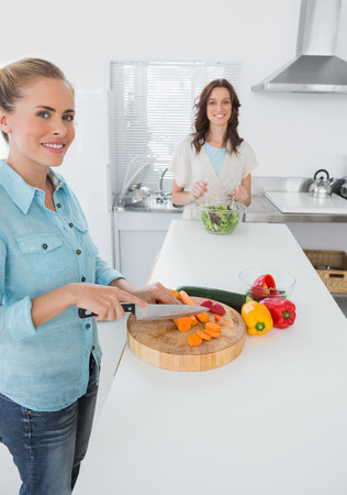 Smiling women cooking together  in the kitchen and looking at camera photo