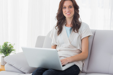Relaxed brunette with laptop on her knees  at home photo