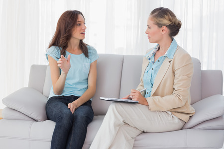 Woman talking to her psychologist  and sitting on the couch photo