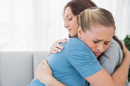 女性は彼女の腕に彼女の友人を取るとソファーに座って