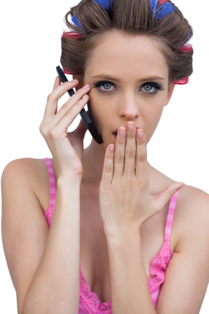 Secretive young wearing hair rollers model on the phone against white background photo