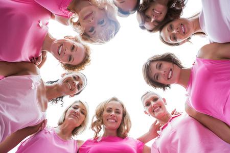 cancer de mama: Mujeres felices sonrientes en c�rculo llevando el rosa para el c�ncer de mama en el fondo blanco