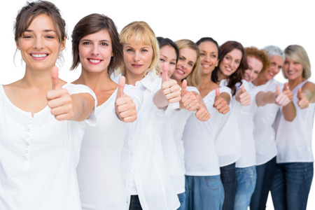 Cheerful casual models posing in a line thumbs up on white background photo