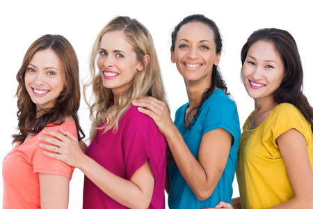 women friends: Smiling models posing with colorful t shirts with hands on shoulders on white background