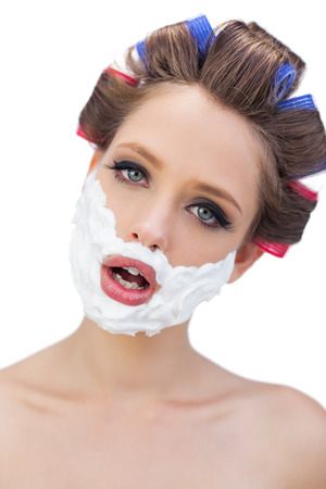 role reversal: Model in hair curlers with shaving foam in close up on white background