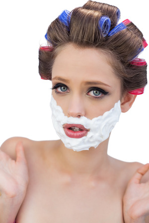 Surprised model in hair curlers posing with shaving foam on white background