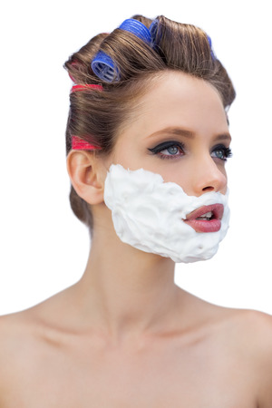 ��role reversal�: Pensive model in hair curlers with shaving foam on white background