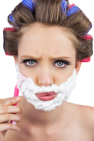 role reversal: Serious model in hair curlers posing with shaving foam and razor on white background