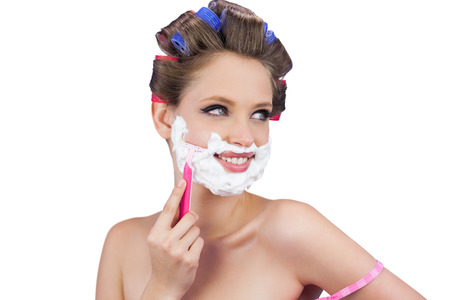 Cheerful lady in hair curlers posing with razor on white background photo