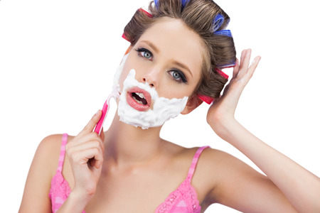 role reversal: Model in hair curlers shaving her face and looking at camera on white background