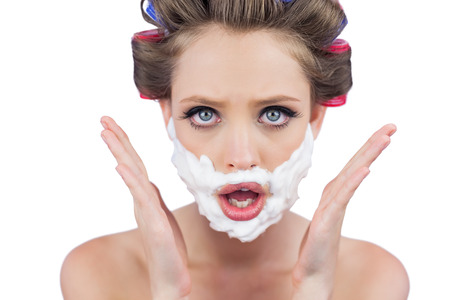 role reversal: Astonished woman posing with shaving foam on face on white background