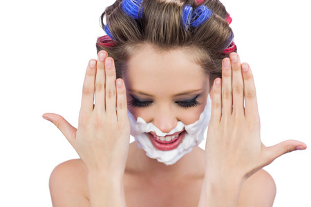 role reversal: Pensive woman with hands up and shaving foam on face on white background
