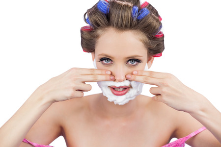 role reversal: Young model with fingers on face and shaving foam on white background