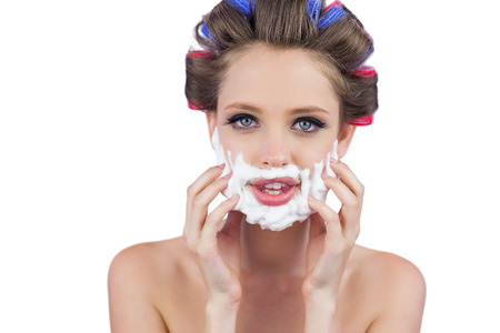 role reversal: Model touching her face with shaving foam on white background