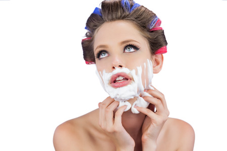 role reversal: Thoughtful young model touching her face with shaving foam on white background Stock Photo