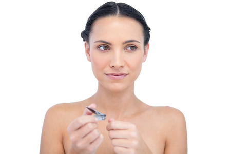 nail clippers: Thoughtful young model using nail clippers on white background