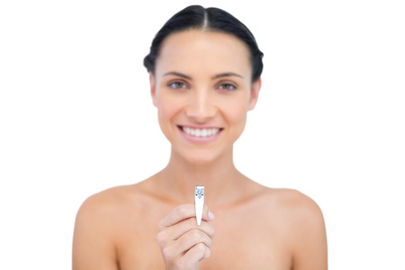 Smiling young brunette holding nail clippers on white background Stock Photo - 25740188
