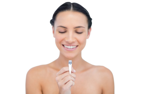 Happy brunette holding and looking at her nail clippers on white background Stock Photo - 25740184