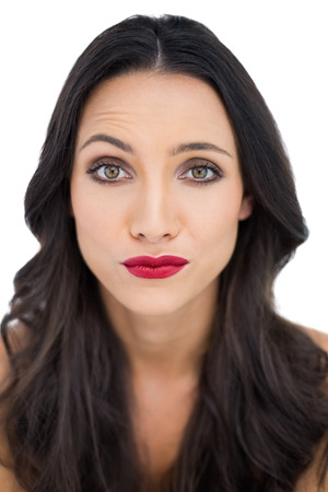 dark haired woman: Doubtful dark haired woman with red lips on white background