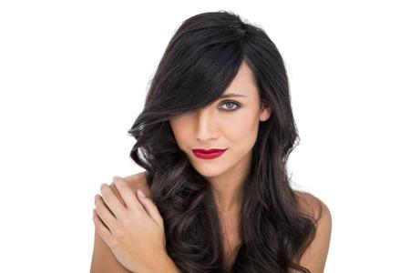 cabello casta�o claro: Morena atractiva que presenta con la mano en su hombro en el fondo blanco