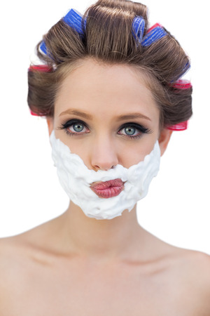 ��role reversal�: Thoughtful model in hair curlers posing with shaving foam on white background