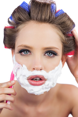 ��role reversal�: Model in hair curlers posing with shaving foam and razor in close up on white background