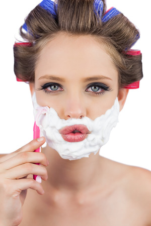 Sexy young model in hair curlers posing with razor looking at camera photo