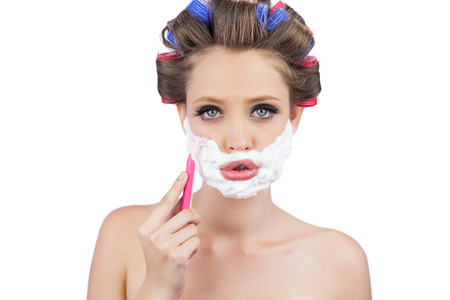 role reversal: Young woman in hair curlers posing with razor on white background Stock Photo