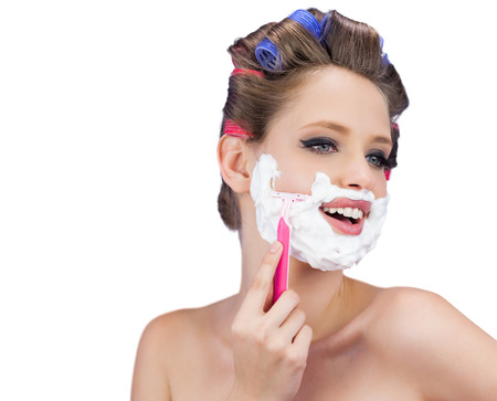 role reversal: Happy model in hair curlers posing with razor on white background Stock Photo