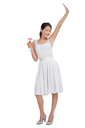 Happy brunette posing with cocktail and looking at camera against white background photo