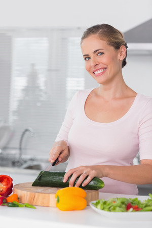 Smiling woman cutting vegetables in kitchen photo