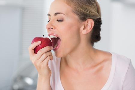 munching: Pretty woman in her kitchen munching apple