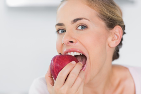 munching: Attractive woman in her kitchen munching apple