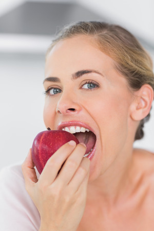 munching: Attractive woman in her kitchen munching red apple