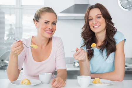Cheerful friends eating cake and having coffee in the kitchen photo