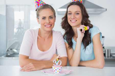 Beautiful women celebrating birthday and wearing party hats photo