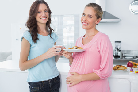 Smling pregnant woman holding cookies and her friend standing in kitchen photo
