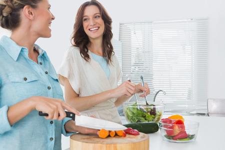 Mujer alegre que se prepara la ensalada juntos en la cocina